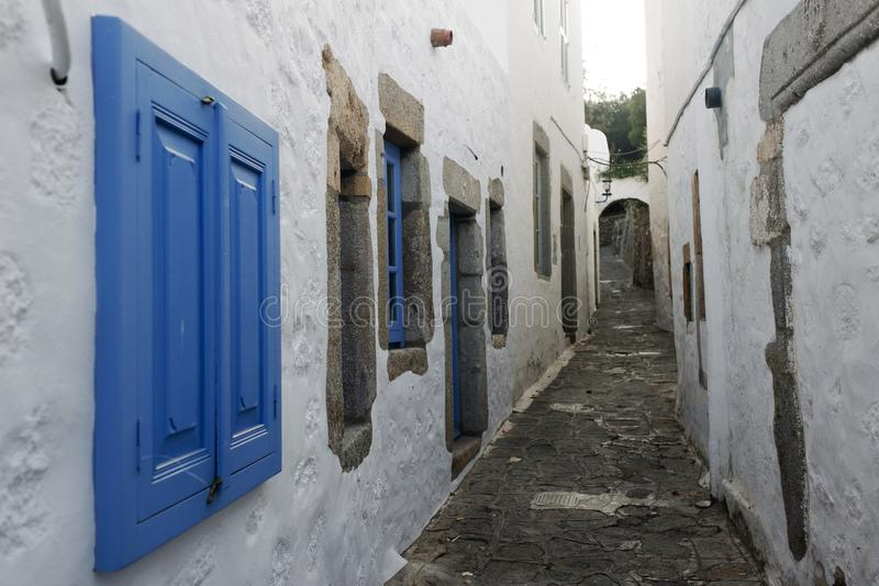 Uma vista de uma rua estreita com arco e as janelas de madeira e as portas com parede branca apedrejam a arquitetura da ilha Patm imagens de stock royalty free