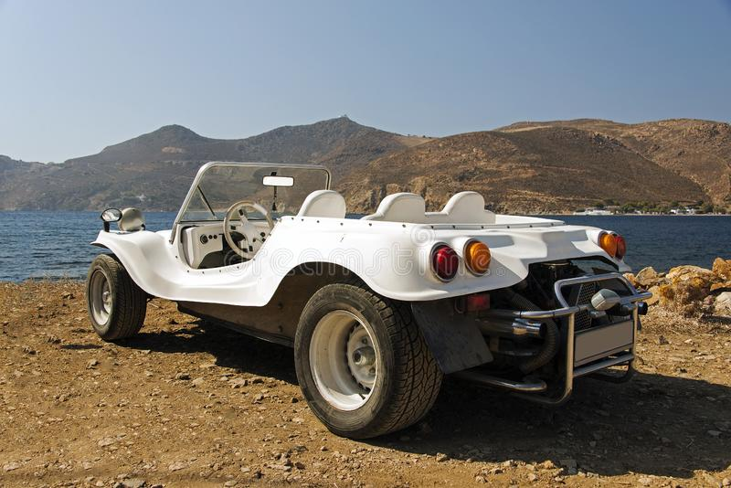Uma vista de um carrinho branco convertível do carro do vintage no beira-mar no verão imagens de stock