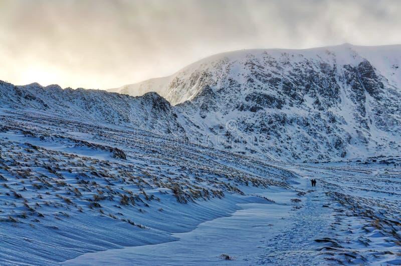 Uma vista de um Helvellyn coberto de neve do trajeto a Tarn vermelho fotografia de stock