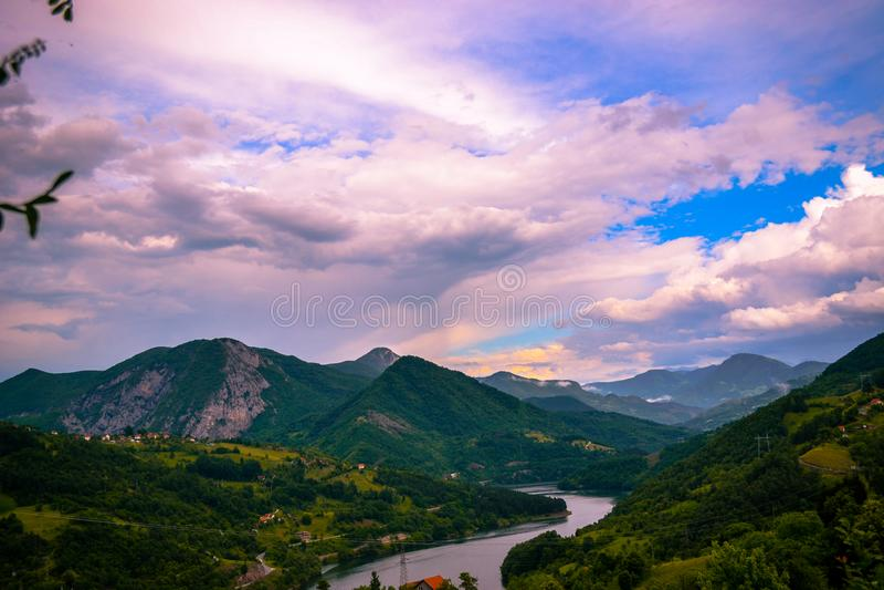 Uma vista de um lugar alto nos montes, nas montanhas e no lago bonitos Por do sol e cor bonita da nuvem no céu no fundo fotografia de stock