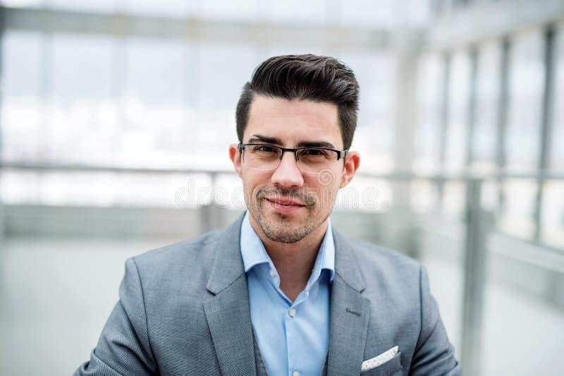 Uma vista dianteira do retrato do homem de negócios novo dentro em um escritório imagem de stock