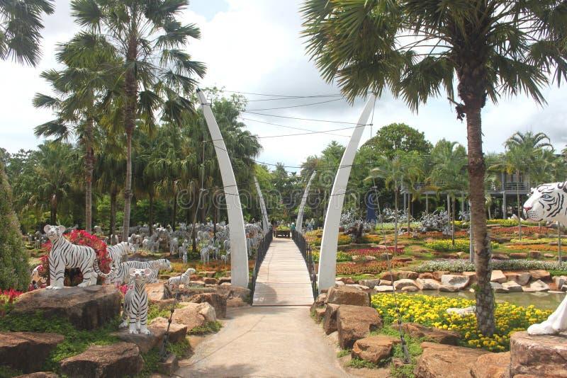 Uma vista dianteira a uma ponte com prado e grama e árvores e pedras no jardim botânico tropical de Nong Nooch perto da cidade de fotografia de stock