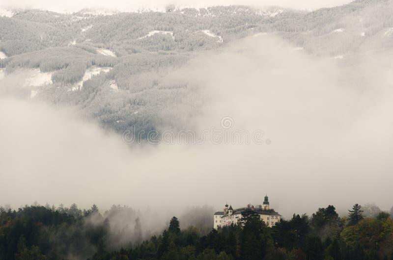 Uma vista do castelo de Ambras em Innsbruck, Áustria cercou por árvores e na perspectiva das montanhas fotos de stock royalty free
