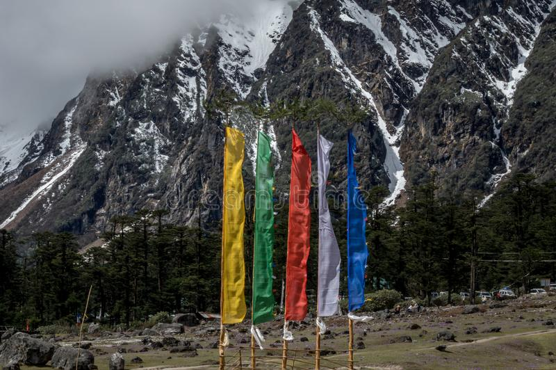 Uma vista do vale de Yumthang na escala Himalaia com as bandeiras religiosas que voam altamente, Índia imagens de stock royalty free
