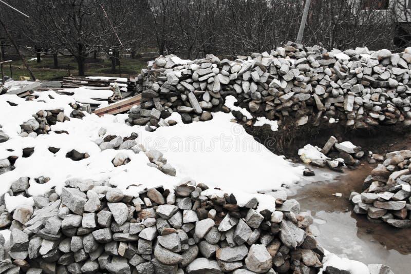 Uma vista dos tijolos sob a neve Pilha da tampa de neve de tijolo Tijolos da construção sob a neve após um ciclone do inverno fotos de stock royalty free