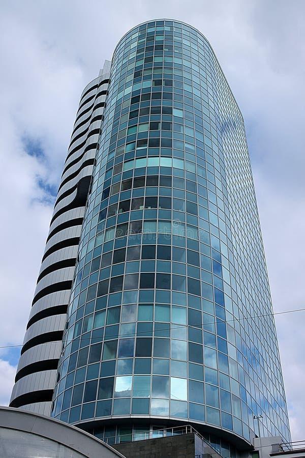 Uma vista inferior do multi-andar bonito espelhou a construção do centro de negócio da cobra no fundo do céu nebuloso sombrio fotos de stock