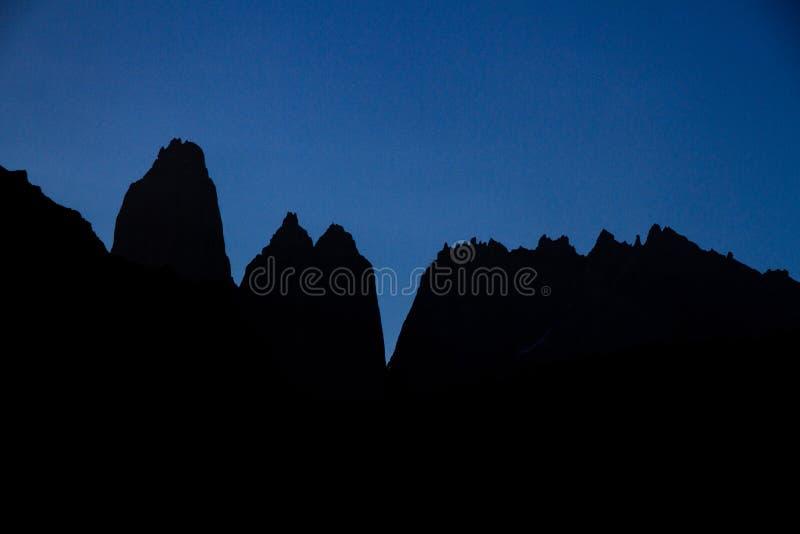 Uma vista mostrada em silhueta das três torres na extremidade da caminhada de W no parque nacional de Torres del Paine imagens de stock