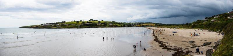Uma vista panorâmica da praia de Inchydoney em um dia nublado com surfar, natação, e apreciar dos povos o tempo morno imagens de stock