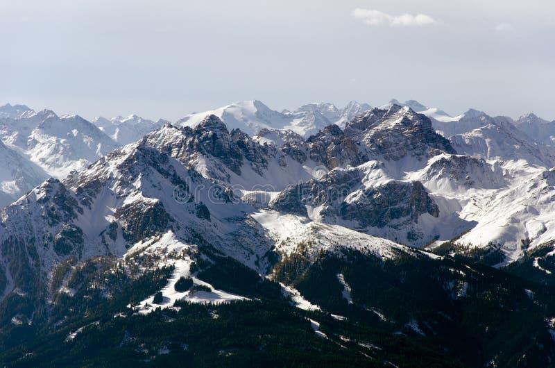 Uma vista panorâmica espaçoso das montanhas dos cumes cobertas parcialmente com a neve foto de stock