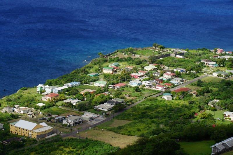 Uma vista superior sobre o litoral da ilha de Kitts de Saint, do St Kitts e do Nevis com construções residenciais, estradas e águ fotos de stock royalty free