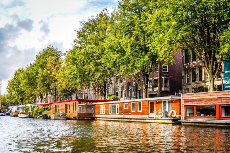 Uma vista típica das casas flutuantes está alinhando o canal de Waalseiland perto da torre de Montelbaans no centro da cidade vel imagens de stock royalty free