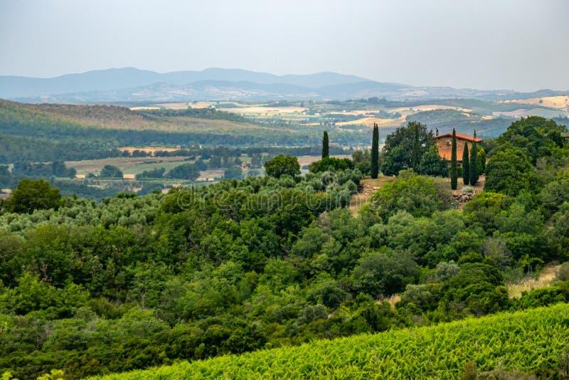 Uma vista típica do campo de Toscânia, Itália, com uma casa e as árvores fotografia de stock royalty free