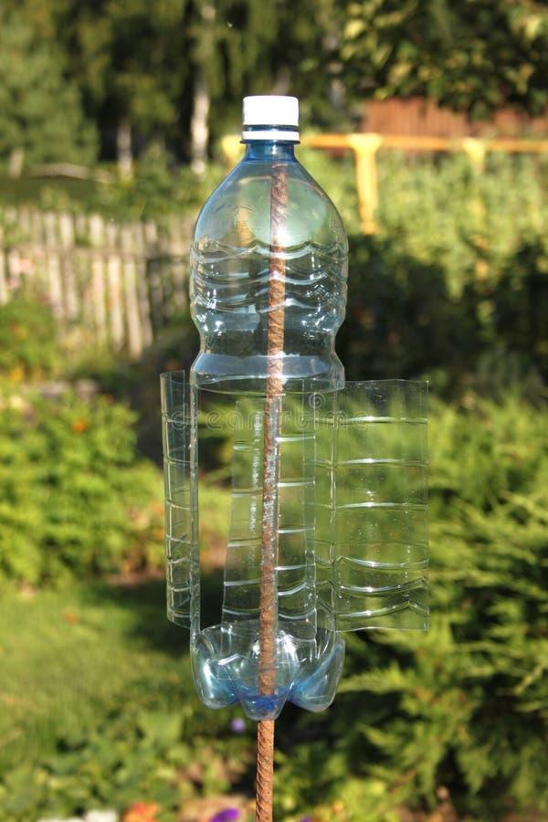 Uma volta plástica da garrafa pelo vento e faz vibrações na terra para toupeiras assustadores e outro roedores imagens de stock