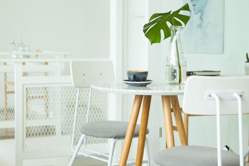 Uma xícara de café é colocada na tabela E flores em um vaso, cafetaria Uso da imagem para o alimento e a bebida foto de stock