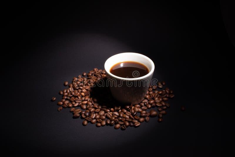 Uma xícara de café é iluminada por um feixe à direita acima imagem de stock royalty free