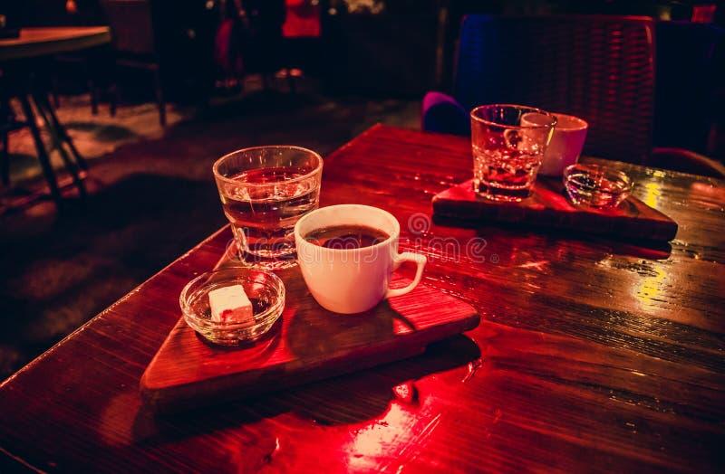 Uma xícara de café branca com loukoum na tabela na noite fotografia de stock royalty free