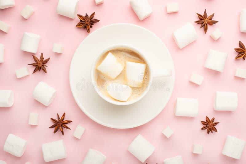 Uma xícara de café branca com marshmallows, e marshmallows, e cubos do açúcar, e aniseas da estrela ao redor em um fundo cor-de-r imagens de stock