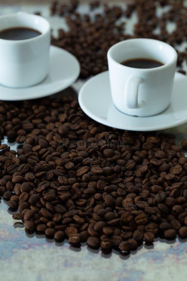 Uma xícara de café cercada de feijões inteiros imagens de stock