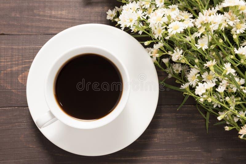 Uma xícara de café com cortador floresce no fundo de madeira imagens de stock