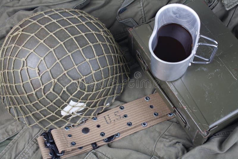 uma xícara de café com equipamento militar do exército dos EUA do período ww2 no uniforme verde fotografia de stock