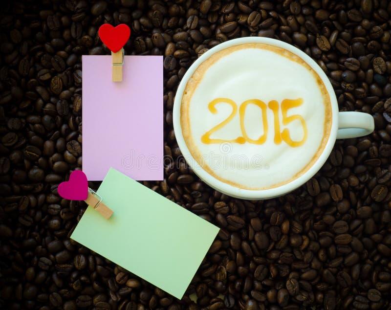 Uma xícara de café com teste padrão da arte 2015 do leite da espuma imagem de stock