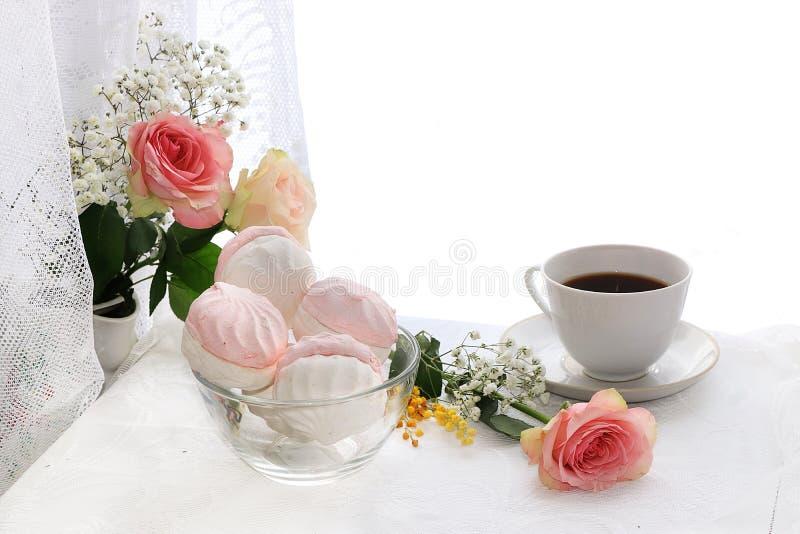 Uma xícara de café e flores em um fundo claro, em desejos do bom dia e no bom dia, imagens de stock