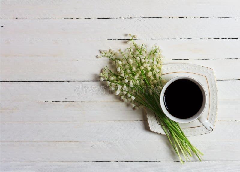 Uma xícara de café e um ramalhete do lírio das flores do vale em uma tabela de madeira branca, vista superior imagem de stock