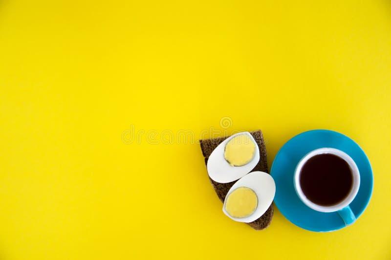 Uma xícara de café e um sanduíche com um ovo e um pão Sanduíche e café da dieta para o café da manhã na manhã em um fundo amarelo imagem de stock royalty free