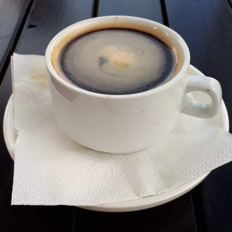 Uma xícara de café em uma placa com uma colher está em uma tabela de madeira fotografia de stock royalty free
