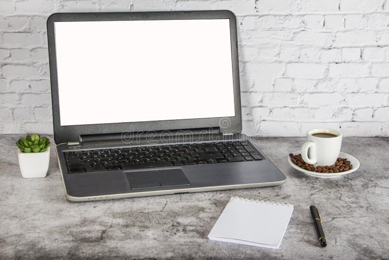 Uma xícara de café em uma tabela branca com um portátil, um bloco de notas e uma pena Conceito ascendente trocista do negócio Lug imagem de stock royalty free