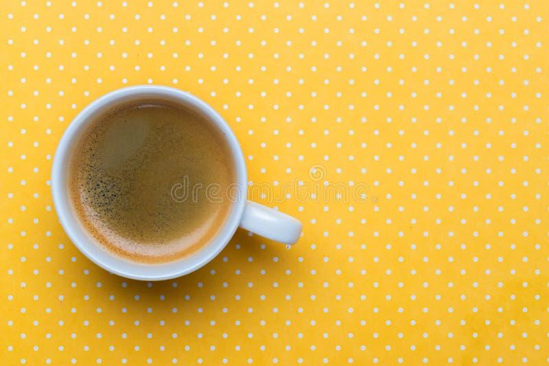 Uma xícara de café em um fundo amarelo do às bolinhas foto de stock royalty free
