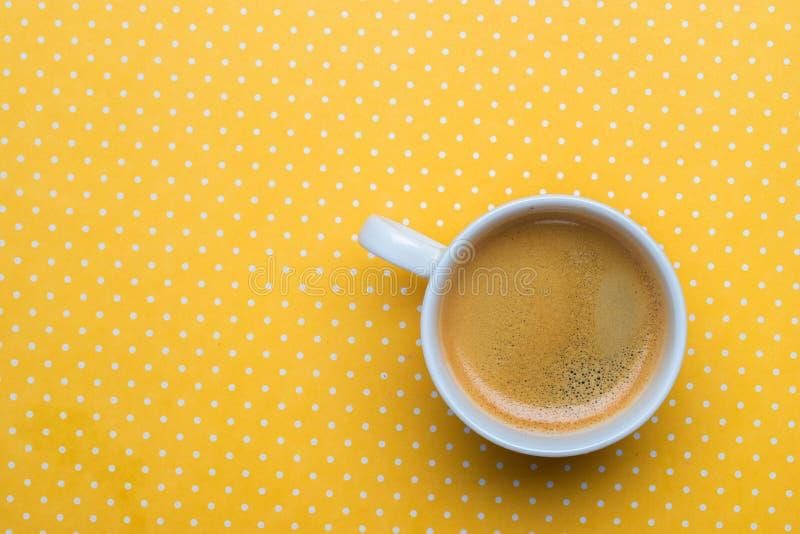 Uma xícara de café em um fundo amarelo do às bolinhas imagens de stock
