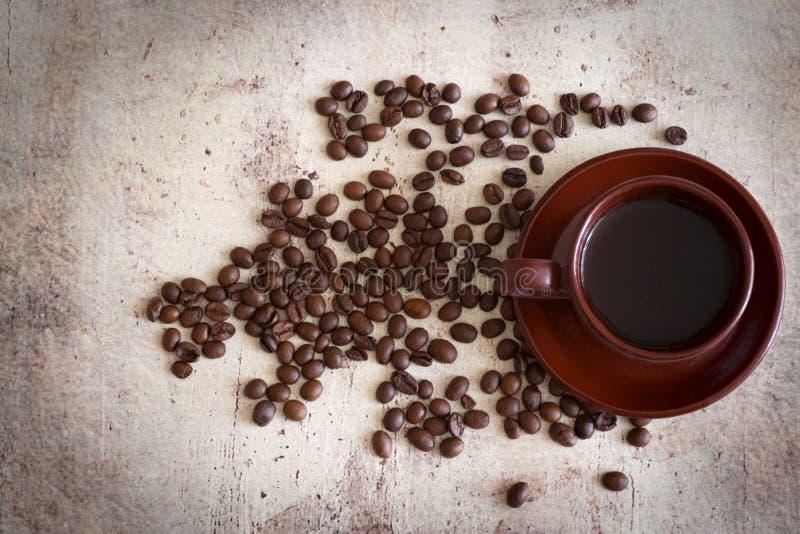 Uma xícara de café na tabela entre os feijões de café dispersados imagem de stock