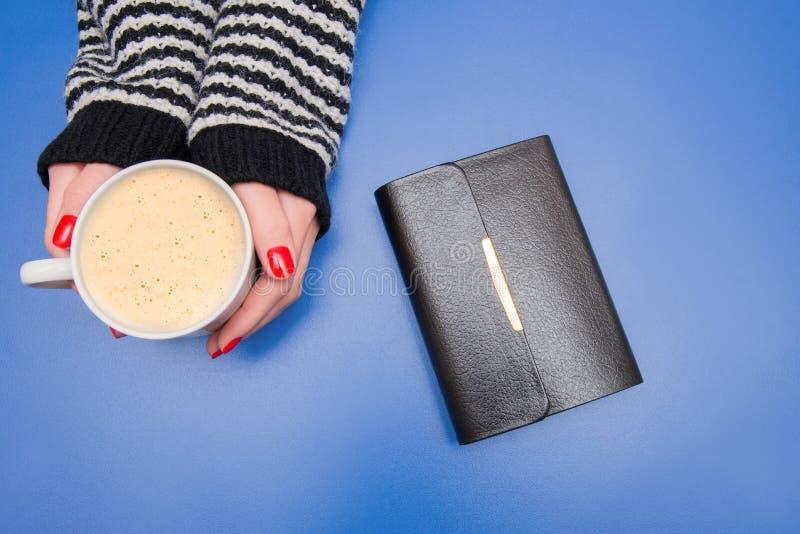 Uma xícara de café nas mãos de uma mulher em um fundo azul fotografia de stock