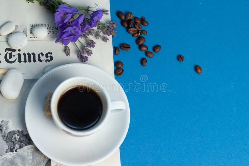 Uma xícara de café perfumada está no jornal, nas flores azuis delicadas e nos feijões de café dispersados em um fundo azul fotos de stock royalty free