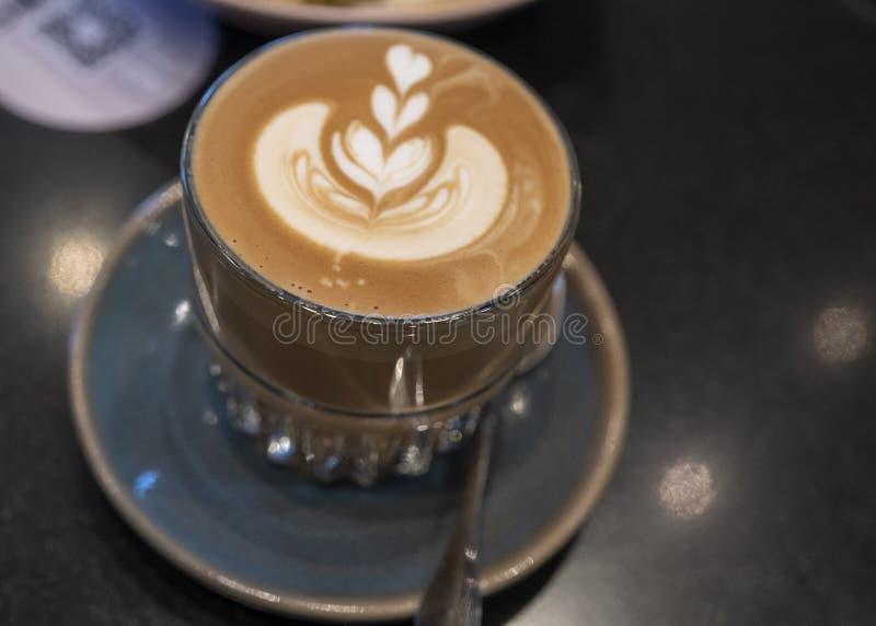 Uma xícara de café saboroso com arte do latte fotografia de stock