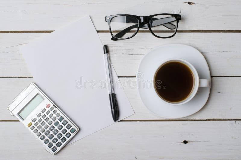 Uma xícara de café, uns vidros, uma calculadora e um papel vazio para seu te imagem de stock royalty free