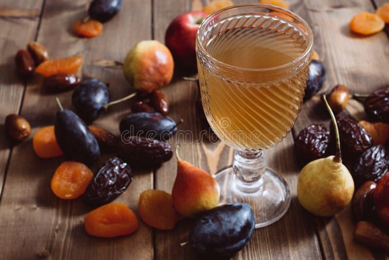Uma xícara de vidro com compota de pera de ameixa de maçã e damascos maduros sobre uma mesa de madeira Sobremesa doce e saudável fotografia de stock