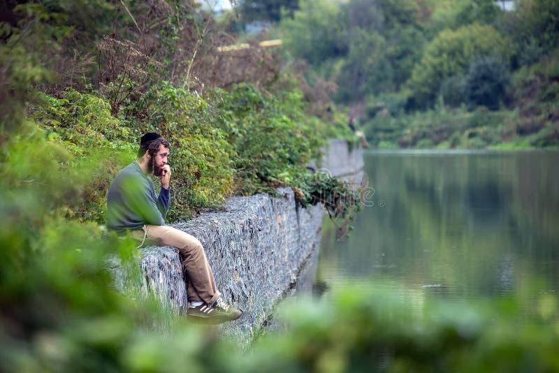 Uman, Ουκρανία, 13 09 2015 το εβραϊκό άτομο σε Kippah κάθεται σκεπτικά στα σύνορα πετρών κοντά στο νερό στοκ φωτογραφία