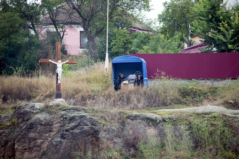 Uman, Ουκρανία, 13 09 2015 τρεις αστυνομικοί κάθονται κάτω από awning κοντά στον ξύλινο σταυρό με τη σταύρωση του Ιησούς Χριστού στοκ εικόνες