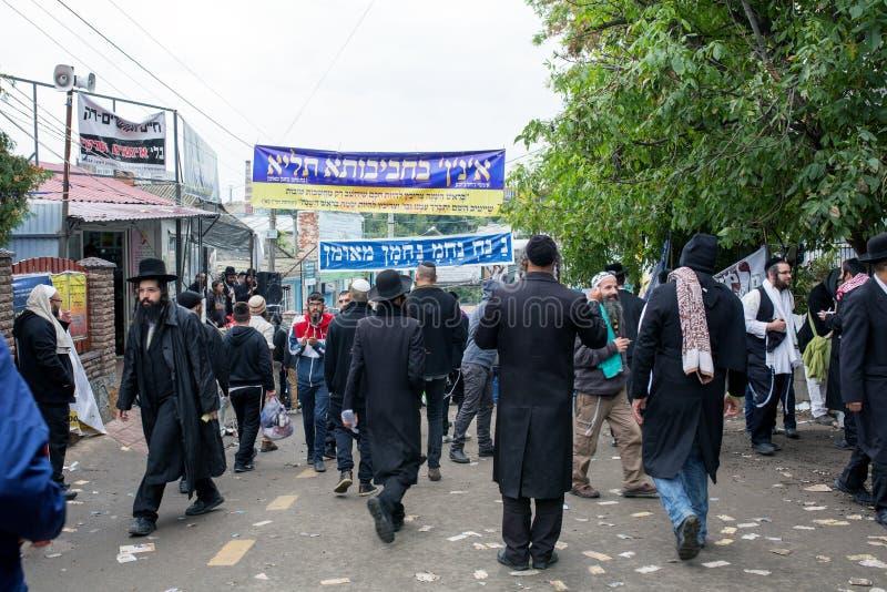 Uman, Украина, 13 09 2015: Много еврейские люди в Kippahs и черных одеждах идут на улицу с сериями writt шильдиков стоковое фото rf