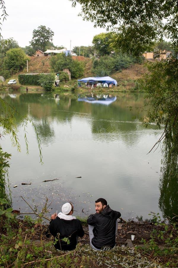 Uman, Ucrânia, 13 09 2015 dois homens do judeu em Kippahs estão sentando-se perto do rio imagem de stock