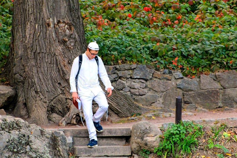 Uman, Ucraina, 22 09 2017 Un giovane ragazzo di Hasid dell'ebreo in vestiti bianchi tradizionali che cammina nel parco con un lib immagine stock libera da diritti