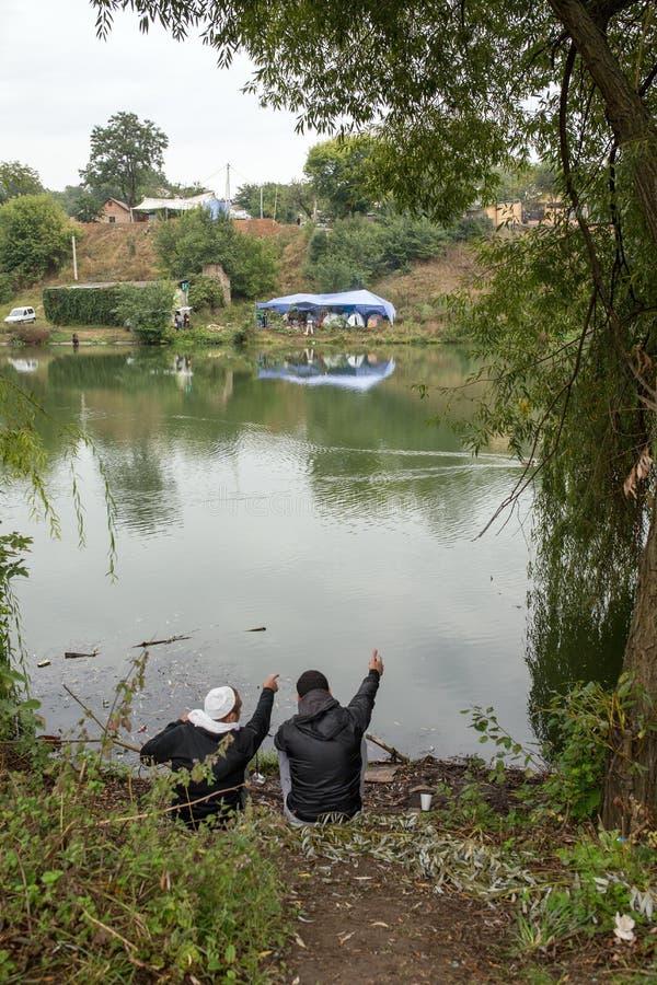 Uman, Ucrania, 13 09 2015 dos hombres del judío en Kippahs se están sentando cerca del río y del punto por sus manos en el otro l fotografía de archivo