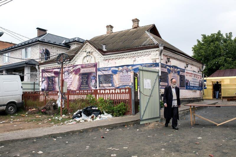Uman, Ucrania, 13 09 2015: El viejo hombre judío en Kippah y ropa negra está saliendo de la yarda cerca de la cual mucha basura foto de archivo libre de regalías