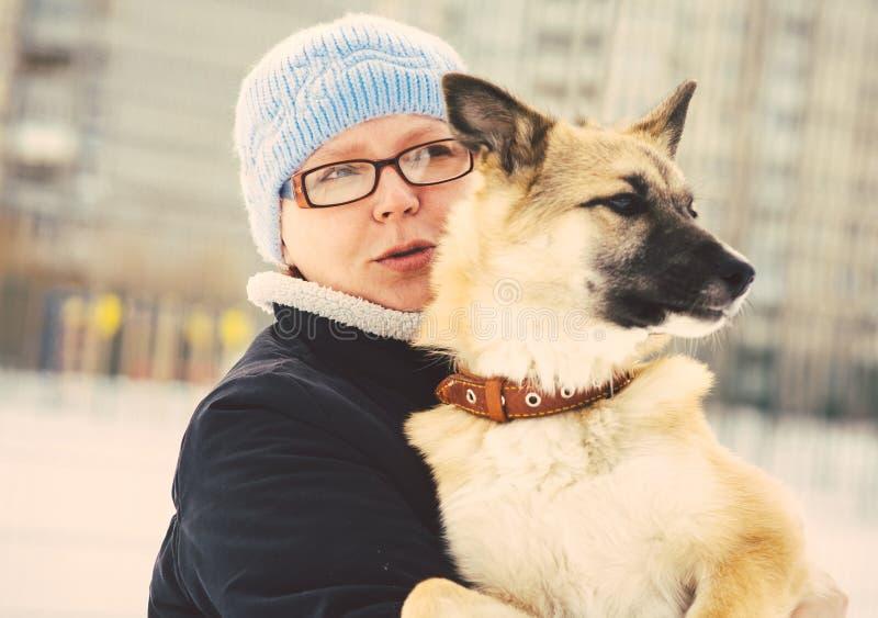 Umarmen des Hundeschäfers Puppy und -frau im Freien lizenzfreie stockfotografie