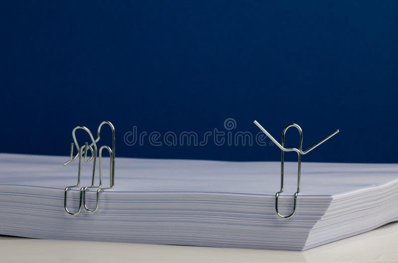 Umarmende Büroklammer-Charaktere und im Ausruf auf Paket Papier stockfoto