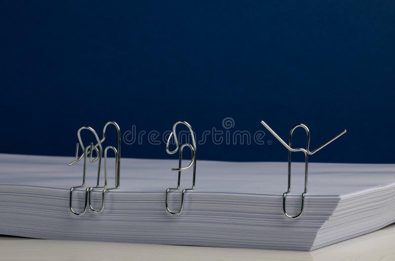 Umarmende Büroklammer-Charaktere und im Ausruf, Gedanke auf Paket Papier lizenzfreies stockbild