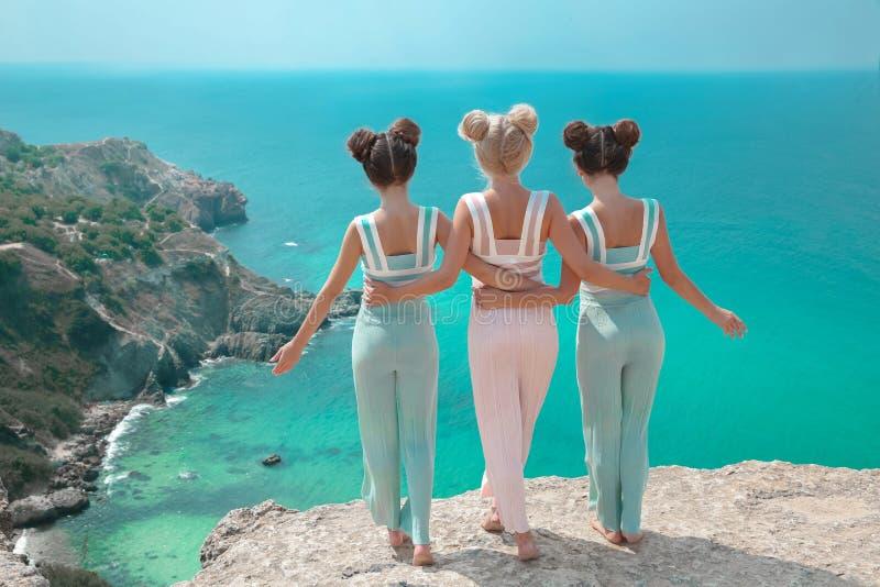 Umarmung mit drei beste Freundinnen Modefrauenkleidung eingestellt Schön lizenzfreies stockbild