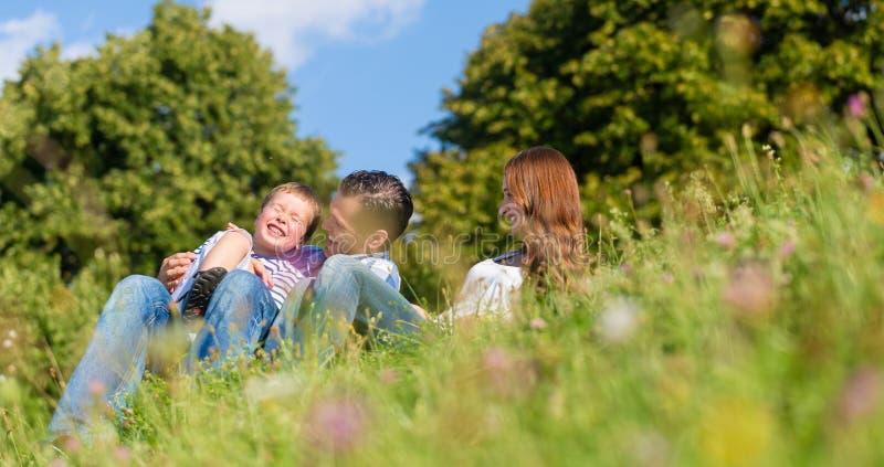 Umarmungsc$sitzen der Familie auf Wiese im Sommer stockbild